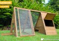 Cluck House chicken coop with large exterior access door opened.